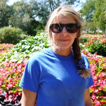 Noelle stands in front of gardens at the Oshawa Valley Botanical Gardens with sunglasses on