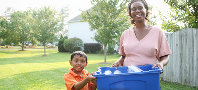 A woman and a young boy holding a recycling bin