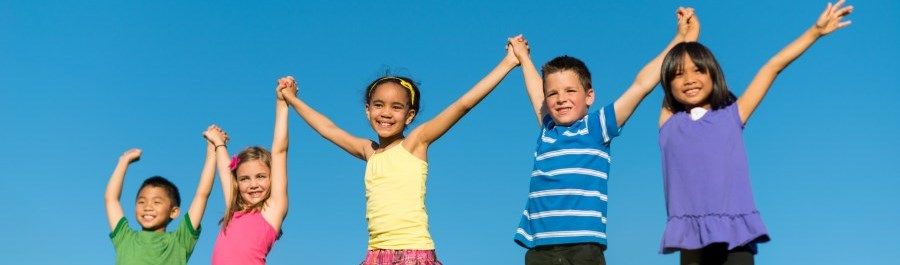 Kids smilling and holding hands on a hill