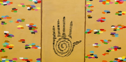 Sand coloured background with sections of multi-coloured pebbles on outside two thirds and black handprint in middle.